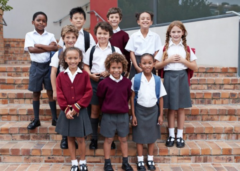 Group of children in school uniform, standing on the steps of a building
