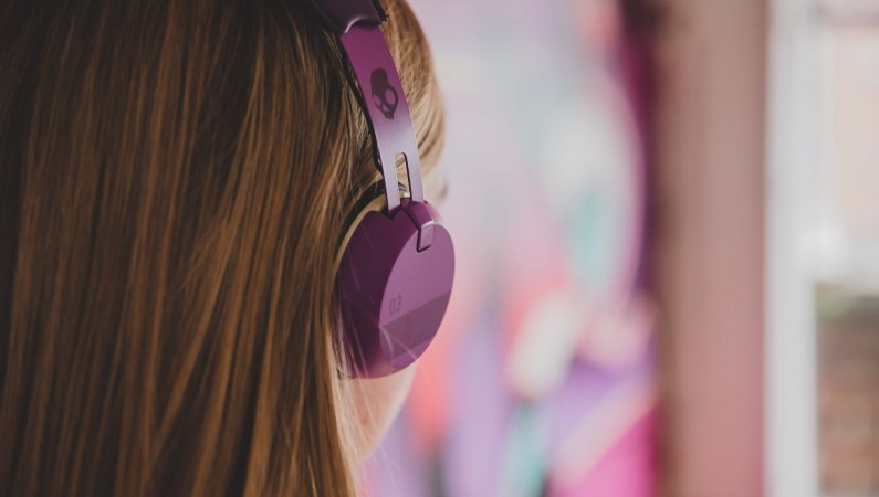 A young woman listening to a podcast on her headphones