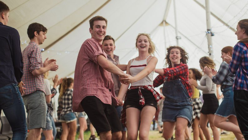Young people enjoying an uproarious barn dance in a marquee at the Dorset Venture Urban Saints Camp this summer (2018)