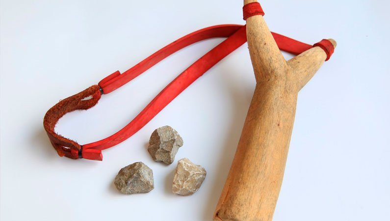 A slingshot with three sharp stones