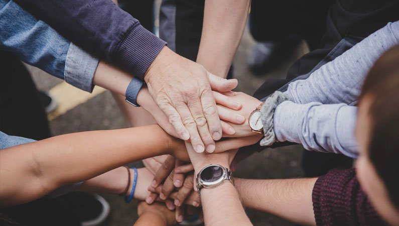 Group of people's hands all reaching in to the centre