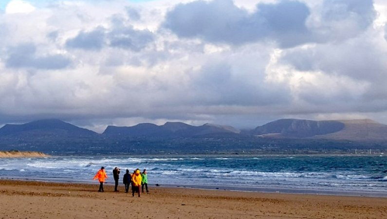 Members of the Urban Saints Impact Team walking along the beach in Anglesey, with dramatic seas and sky behind them - during the Impact Team's time away together in October 2019