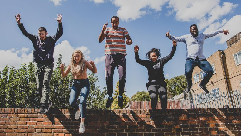 Five people jumping from a brick wall