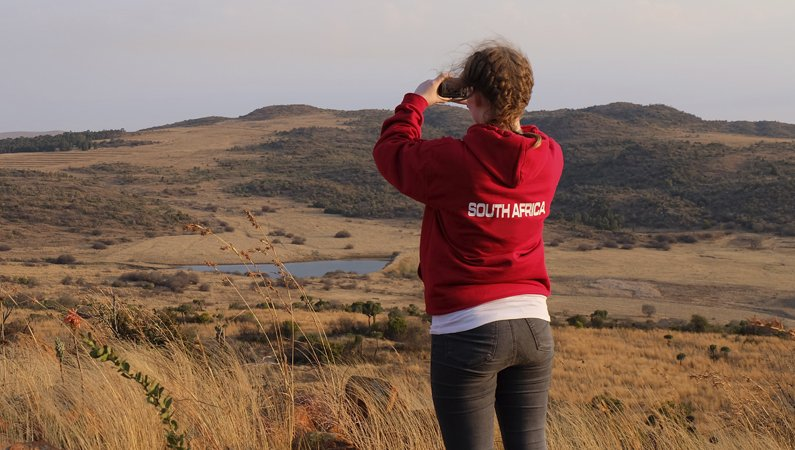 Girl wearing a red hoodie taking a photograph in South Africa