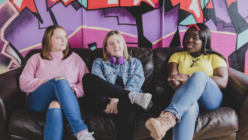 Three young people siting together on a sofa with graffiti on the wall behind them.