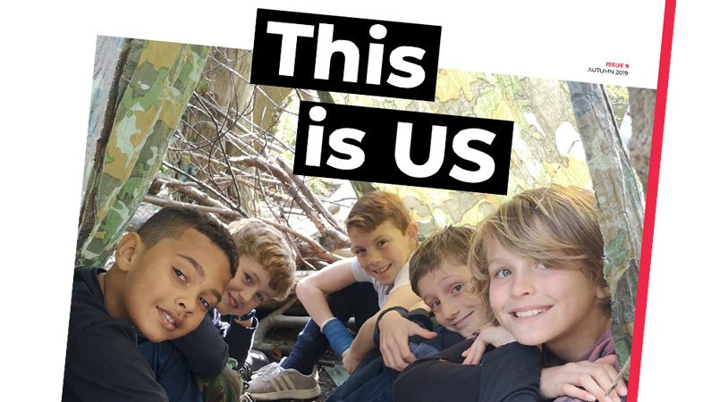 A close-up of the latest edition of Urban Saints' 'This is US' magazine, with a group of lads inside a homemade woodland shelter