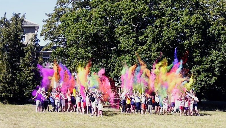 Young people throw paint in the air to celebrate 70 years of Camps at Urban Saints Westbrook on the Isle of Wight