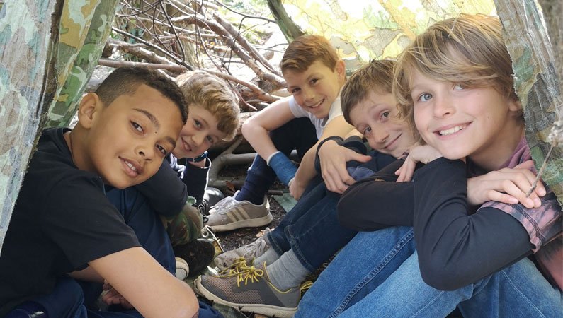 Group of lads in a shelter built in the woods at Urban Saints Westbrook