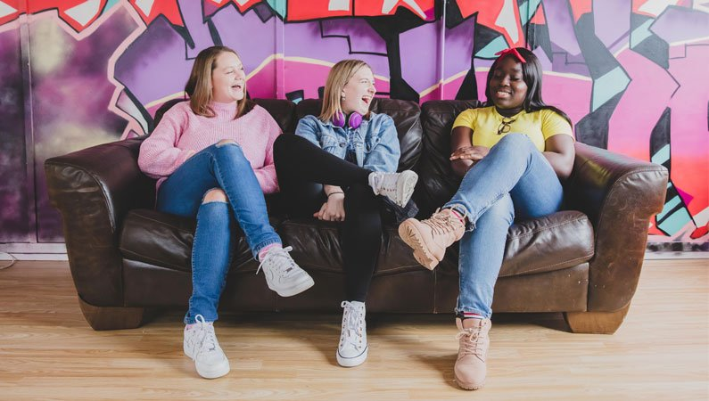 Three girls sat on a sofa chatting and laughing
