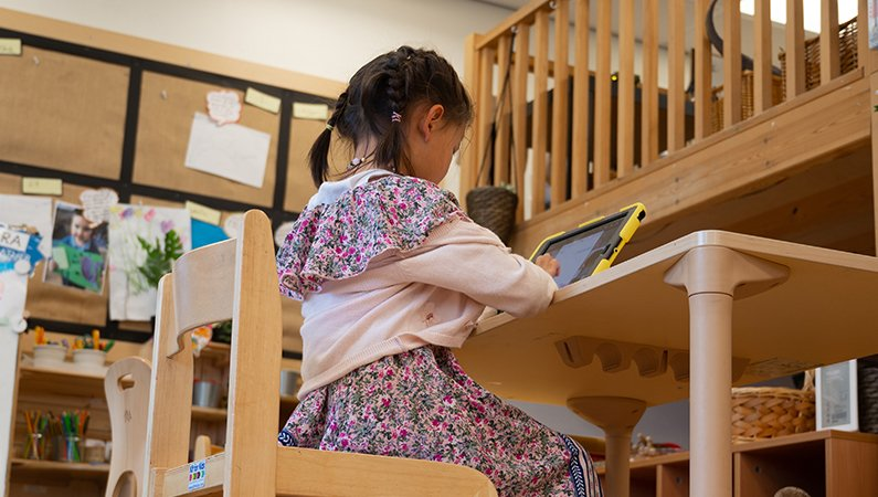 young girl in a classroom space using a electronic tablet