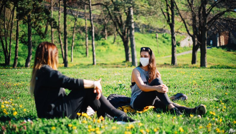 Young people meeting in the park socially distanced and with face coverings during the pandemic