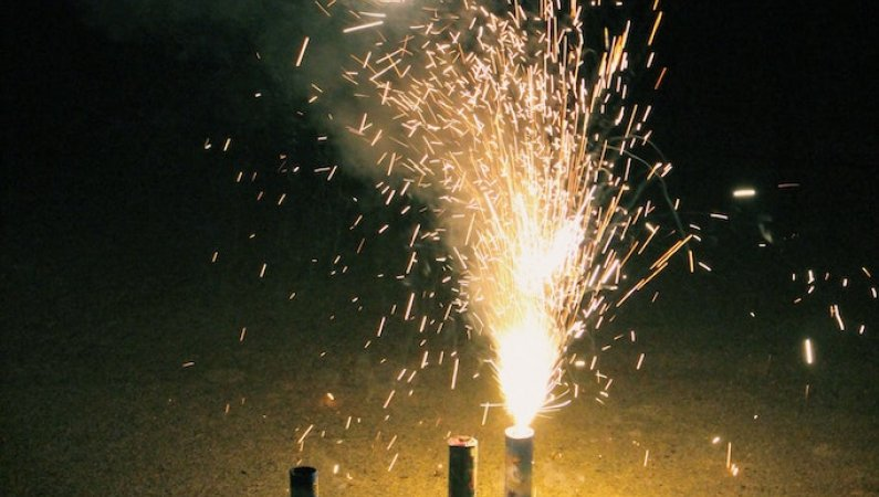 A firework burns and sparks in a local community street