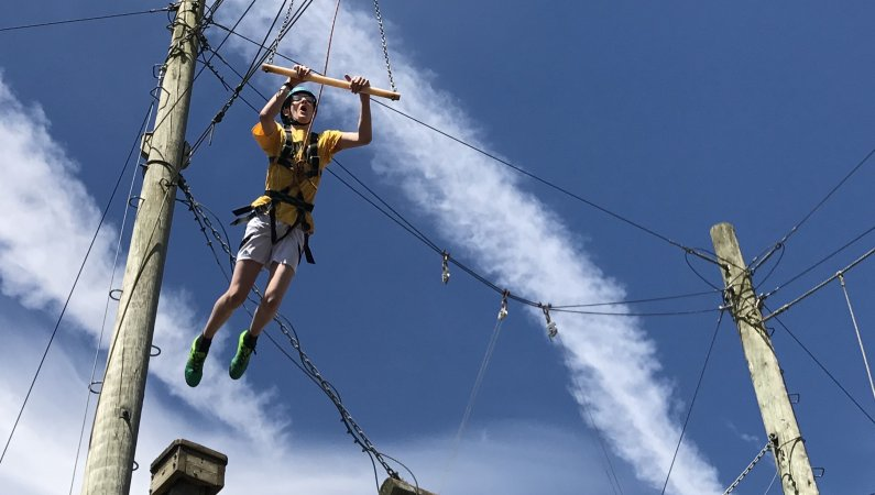 Young person taking the leap on a high-ropes course